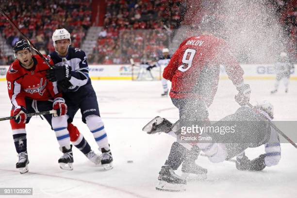Mathieu Perreault of the Winnipeg Jets is checked by Dmitry Orlov of the Washington Capitals during the first period at Capital One Arena on March 12...
