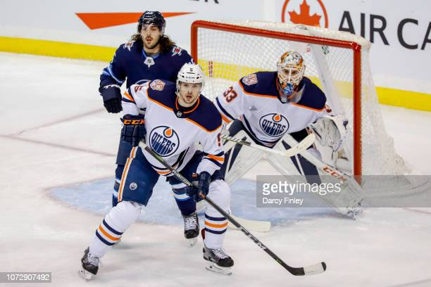 Mathieu Perreault of the Winnipeg Jets Kevin Gravel and goaltender Cam Talbot of the Edmonton Oilers keep an eye on the play during first period...