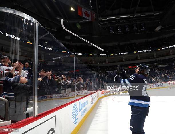 Mathieu Perreault of the Winnipeg Jets launches a souvenir stick over the glass after receiving first star honors following a 51 victory over the...