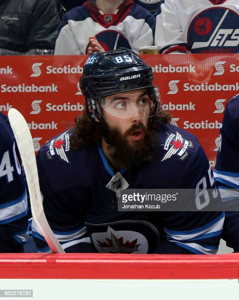 Mathieu Perreault of the Winnipeg Jets looks on from the bench prior to puck drop against the Chicago Blackhawks at the Bell MTS Place on March 15...