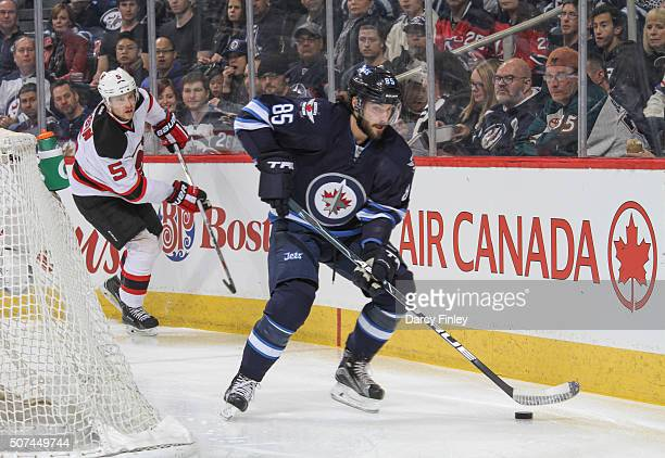Mathieu Perreault of the Winnipeg Jets plays the puck around the net as Adam Larsson of the New Jersey Devils gives chase during first period action...