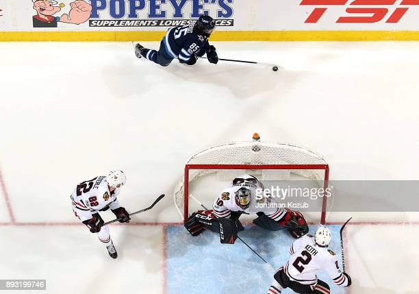Mathieu Perreault of the Winnipeg Jets plays the puck behind the net as Jordan Oesterle goaltender Corey Crawford and Duncan Keith of the Chicago...