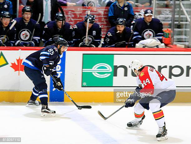 Mathieu Perreault of the Winnipeg Jets plays the puck down the ice as Erik Gudbranson of the Florida Panthers defends during second period action at...