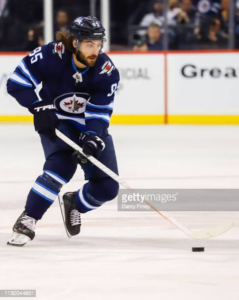 Mathieu Perreault of the Winnipeg Jets plays the puck down the ice during first period action against the New York Rangers at the Bell MTS Place on...