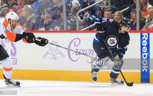 Mathieu Perreault of the Winnipeg Jets plays the puck up the ice as Sean Couturier of the Philadelphia Flyers gives chase during thirdperiod action...