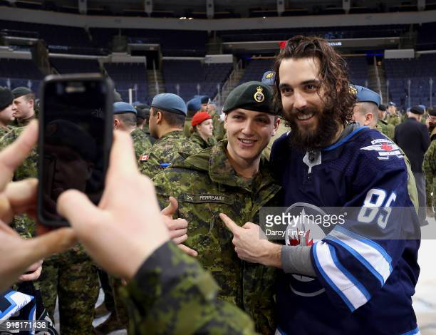 Mathieu Perreault of the Winnipeg Jets poses with a member of the Canadian Armed Forces following NHL action against the Arizona Coyotes on Canadian...