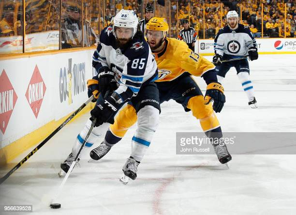 Mathieu Perreault of the Winnipeg Jets skates against Nick Bonino of the Nashville Predators in Game Five of the Western Conference Second Round...