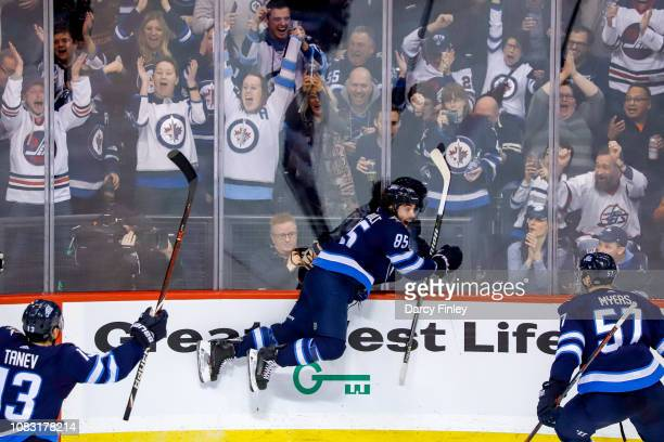 Mathieu Perreault of the Winnipeg Jets takes a leap into the glass after scoring a second period goal against the Vegas Golden Knights at the Bell...