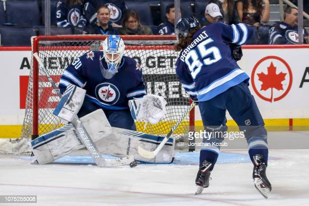 Mathieu Perreault of the Winnipeg Jets takes a shot on goaltender Laurent Brossoit during the pregame warm up prior to NHL action against the Calgary...