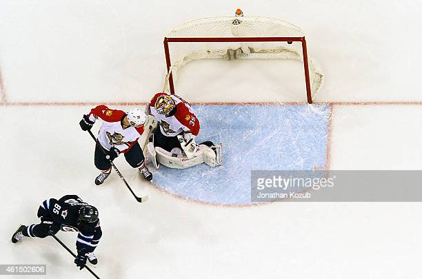 Mathieu Perreault of the Winnipeg Jets tips the puck over goaltender Al Montoya of the Florida Panthers and under the crossbar for his hat trick goal...