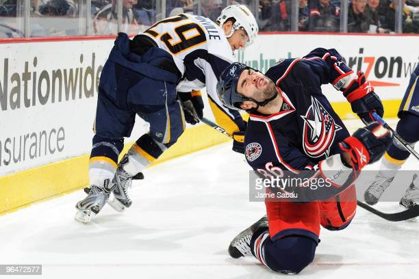 Mathieu Roy of the Columbus Blue Jackets falls after getting hit by a high stick by Jason Pominville of the Buffalo Sabres during the third period on...