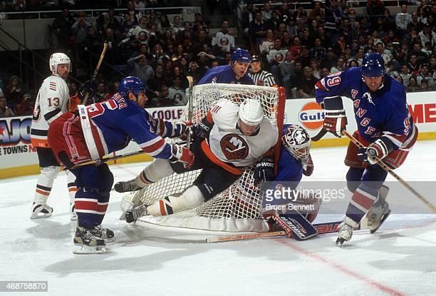 Mathieu Schneider of the New York Rangers checks Mariusz Czerkawski of the New York Islanders into the net as goalie Mike Richter and Wayne Gretzky...