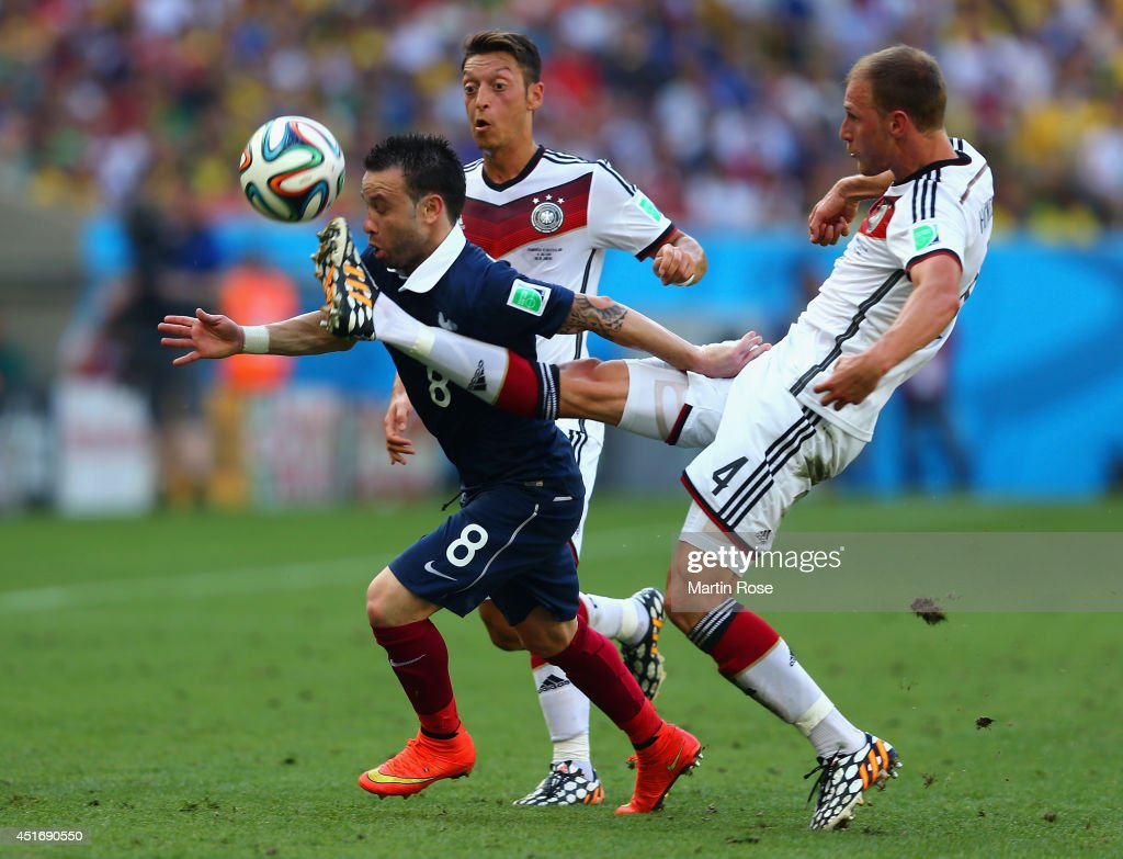 Mathieu Valbuena of France is challenged by Mesut Oezil (C) and Benedikt Hoewedes of Germany during the 2014 FIFA World Cup Brazil Quarter Final match between France and Germany at Maracana on July 4, 2014 in Rio de Janeiro, Brazil.