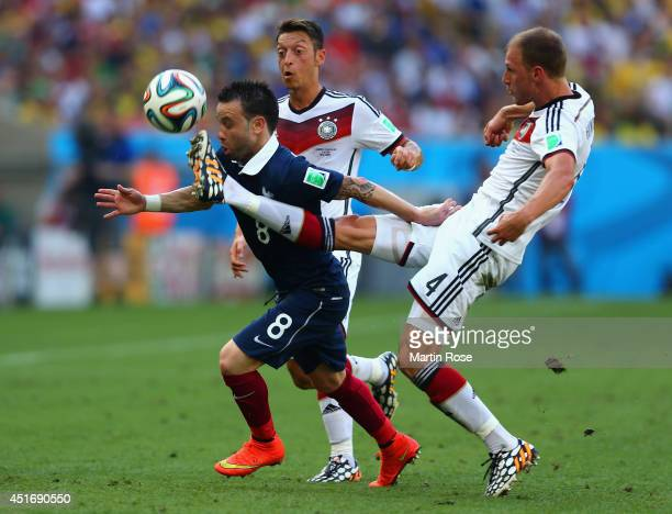 Mathieu Valbuena of France is challenged by Mesut Oezil and Benedikt Hoewedes of Germany during the 2014 FIFA World Cup Brazil Quarter Final match...