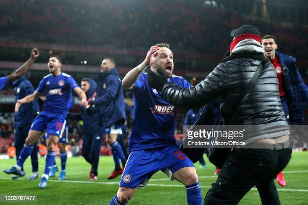 Mathieu Valbuena of Olympiacos celebrates their victory with a fan during the UEFA Europa League round of 32 second leg match between Arsenal FC and...