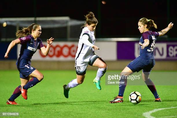Mathilde Bourdieu of Paris FC slips between Eve Perisset of PSG and Erika Cristiano Dos Santos of PSG during the Women's Division 1 match between...