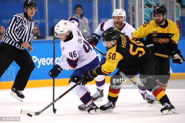 Mathis Olimb of Norway competes for the puck with Patrick Hager of Germany in overtime during the Men's Ice Hockey Preliminary Round Group B game on...
