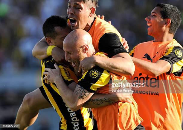 Matias Aguirregaray of Peñarol celebrates with teammates after scoring the first goal of his team during a match between Nacional and Peñarol as part...