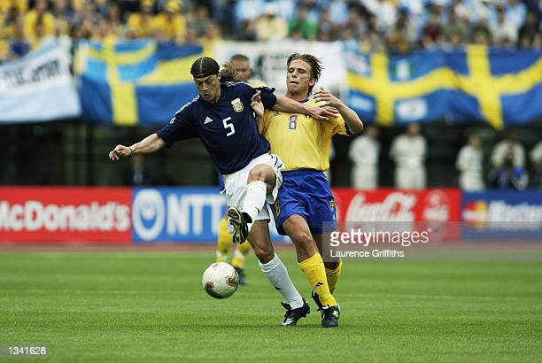 Matias Almeyda of Argentina is tackled by Anders Svensson of Sweden during the Group F match of the World Cup Group Stage played at the Miyagi...