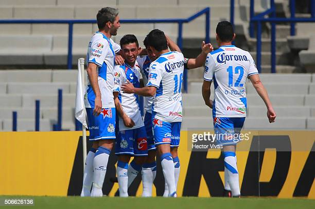 Matias Alustiza of Puebla celebrates with his teammates after scoring the first goal of his team during the 3rd round match between Pumas UNAM and...