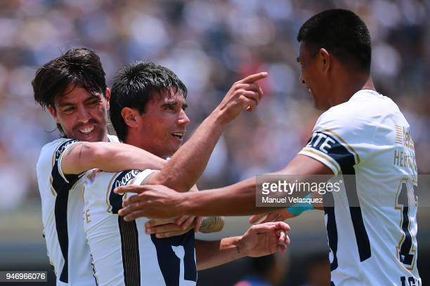 Matias Alustiza of Pumas celebrates with teammates Mauro Formica and Jesus Gallardo after scoring the second goal of his team during the 15th round...
