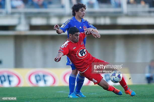 Matias Corujo of Universidad de Chile fights for the ball with Sebastian Varas of Ñublense during a match between Nublense and Universidad de Chile...
