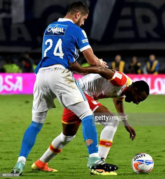 Matias dos Santos of Millonarios vies for the ball with Juan David Valencia of Independiente Santa Fe during the first leg match between Millonarios...