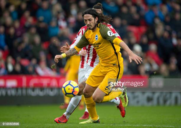 Matias Ezequiel Schelotto of Brighton and Hove Albion runs with the ball under pressure from Maxim ChoupoMoting of Stoke City during the Premier...
