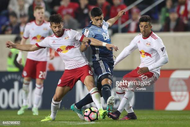 Matias Laba of Vancouver Whitecaps is tackled by Felipe Martins of New York Red Bulls watched by Gonzalo Veron of New York Red Bulls during the New...