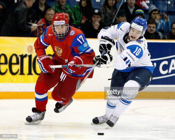 Matias Myttynen of Team Finland skates with the puck while being defended by Yevgeni Kuznetsov of Team Russia during the 2010 IIHF World Junior...