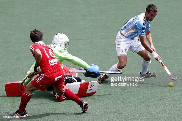 Matias Paredes of Argentina scores while passing England's goalkeeper George Pinner and player Adam Dixon during the Field Hockey World Cup match...