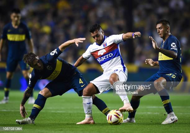 Matias Perez Garcia of Tigre fights for the ball with Julio Buffarini and Agustin Almendra of Boca Juniors during a match between Boca Juniors and...