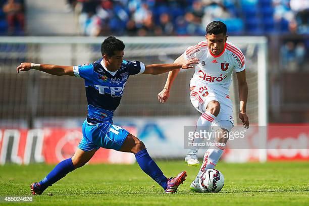 Matias Rodriguez of U de Chile fights for the ball with Claudio Jopia of San Marcos de Arica during a match between San Marcos de Arica and U de...