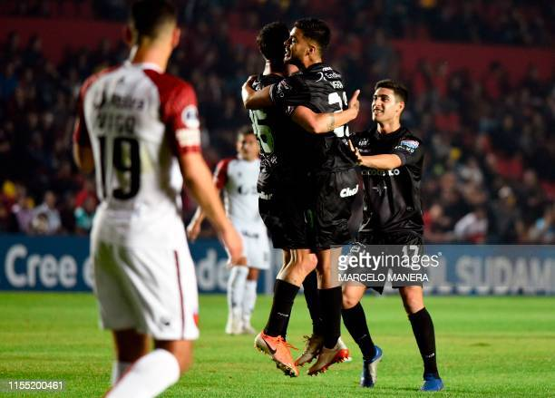 Matias Romero of Argentina's Argentinos Juniors celebrates with teammates after scoring against Argentina's Colon vie for the ball during the Copa...