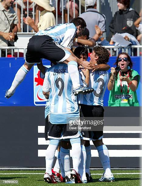 Matias Sanchez of Argentina leaps on to a pile of teammates after Sergio Aguero scored to tie the game against the Czech Republic during their FIFA...