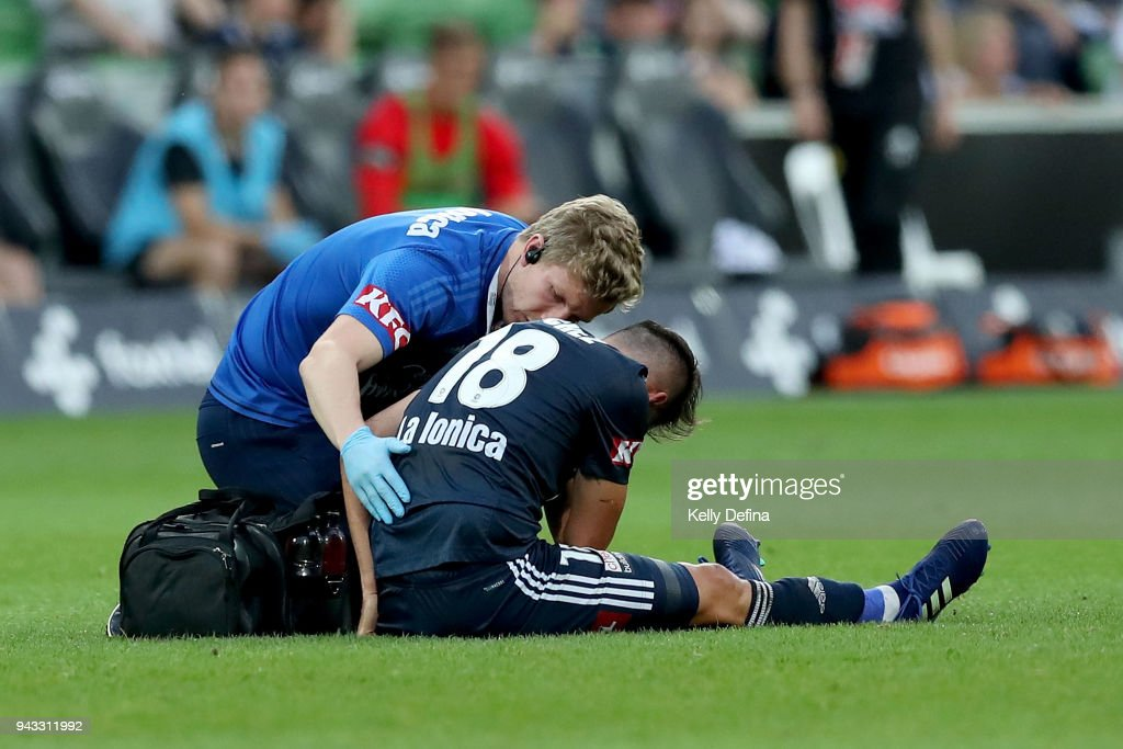 Matias Sanchez of Melbourne Victory receives medical attention after a collision during the round 26 A-League match between the Melbourne Victory and the Wellington Phoenix at AAMI Park on April 8, 2018 in Melbourne, Australia.