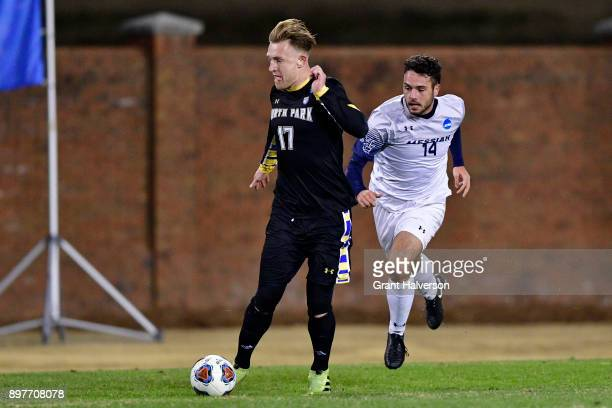 Matias Warp of North Park University dribbles past Ben Haines of Messiah College during the Division III Men's Soccer Championship held at UNC...