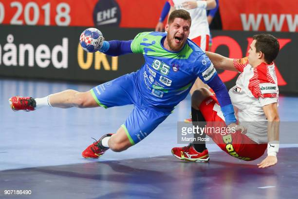 Matic Suholeznik of Slovenia is challenged by Rasmus Lauge Schmidt of Denmark during the Men's Handball European Championship main round group 2...