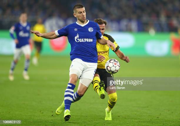Matija Nastasic of FC Schalke shoots is challenged by Mario Gotze of Borussia Dortmund during the Bundesliga match between FC Schalke 04 and Borussia...