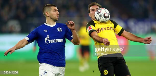 Matija Nastasic of Schalke challenges Mario Goetze of Dortmund during the Bundesliga match between FC Schalke 04 and Borussia Dortmund at...