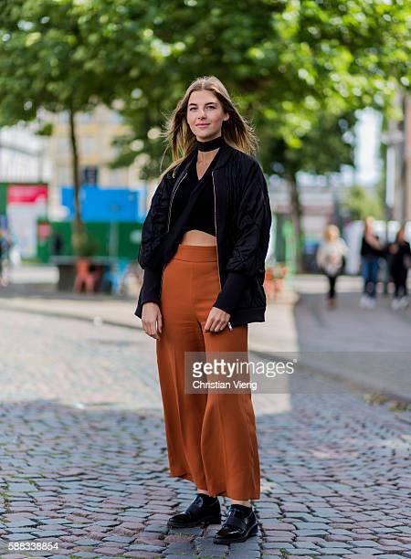 Matilda Fondell wearing a black bomber jacket a choker black copped top orange pants black belt bag and black shoes outside Revolver Fair during the...