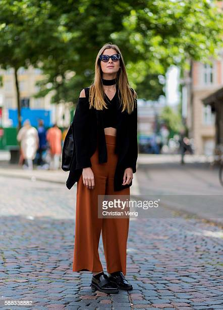 Matilda Fondell wearing a black choker black copped top orange pants black belt bag and black shoes outside Revolver Fair during the first day of the...