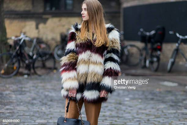 Matilda Fondell wearing a multi colour striped fake fur coat brown pants black bag black leather shoes during the Copenhagen Fashion Week...