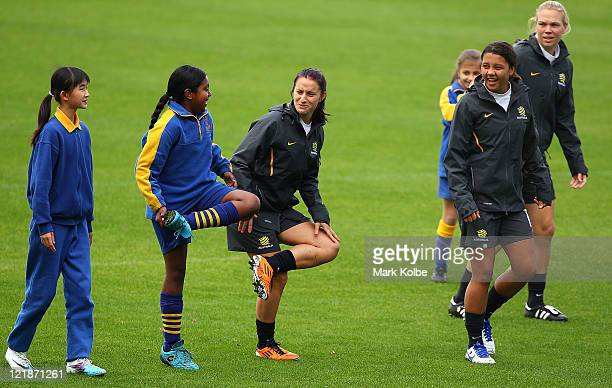 Matilda speak to the children on as they warmup with a students from Carlton South Public School during an Australian Matildas training session at...