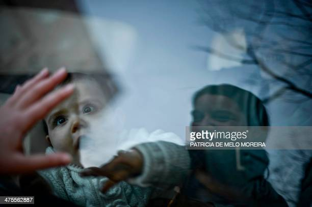 Matilde plays with her daughter Carolina through the car window as her girlfriend Olga holds her inside the car in Lisbon on February 23 2014 Matilde...