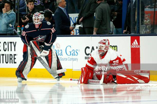 Matiss Kivlenieks of the Columbus Blue Jackets and Jimmy Howard of the Detroit Red Wings warm up prior to the start of the game on February 7 2020 at...
