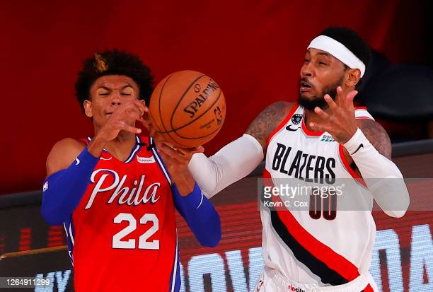 Matisse Thybulle of the Philadelphia 76ers and Carmelo Anthony of the Portland Trail Blazers go after a loose ball during the third quarter at Visa...