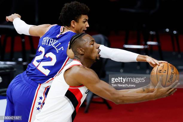 Matisse Thybulle of the Philadelphia 76ers and Harry Giles III of the Portland Trail Blazers reach for the ball during the second quarter at Wells...