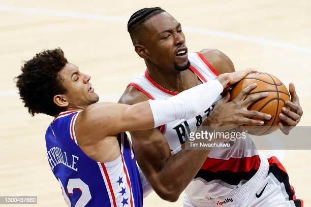 Matisse Thybulle of the Philadelphia 76ers and Harry Giles III of the Portland Trail Blazers reach for the ball during the third quarter at Wells...
