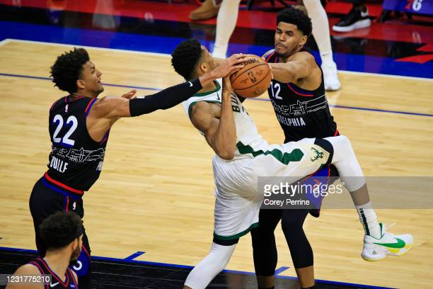 Matisse Thybulle of the Philadelphia 76ers and Tobias Harris frustrate Giannis Antetokounmpo of the Milwaukee Bucks during the second quarter at the...